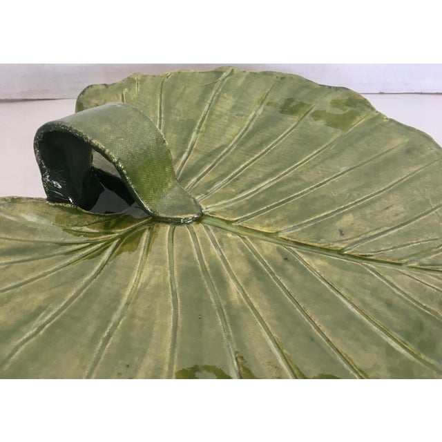 Super studio pottery in a leaf shape serving platter with a raised stem to carry.