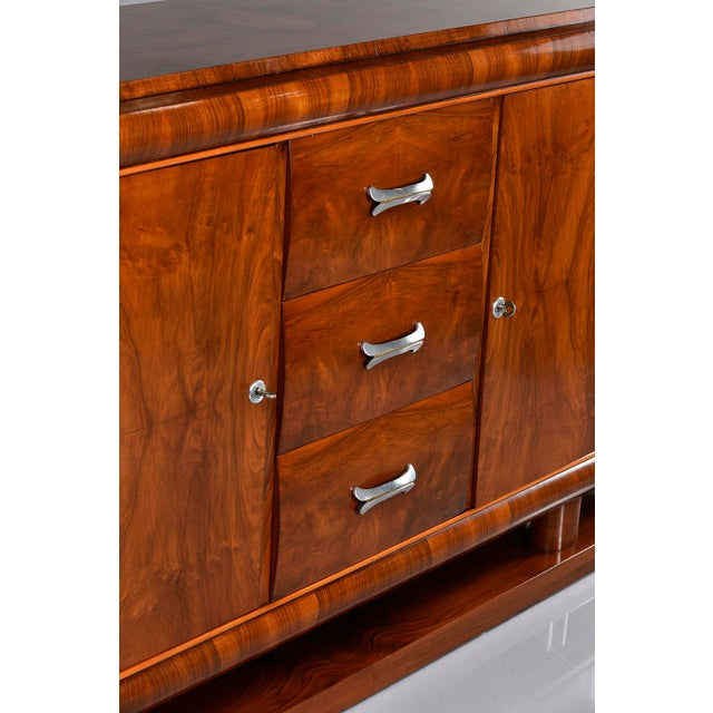 Circa 1930s French Deco era sideboard in walnut with three center drawers flanked by locking cabinets with single internal...