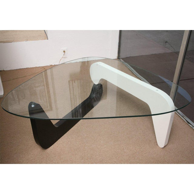 This is a graceful organic Noguchi coffee table lacquered in black and white. Beautiful element in home or office.