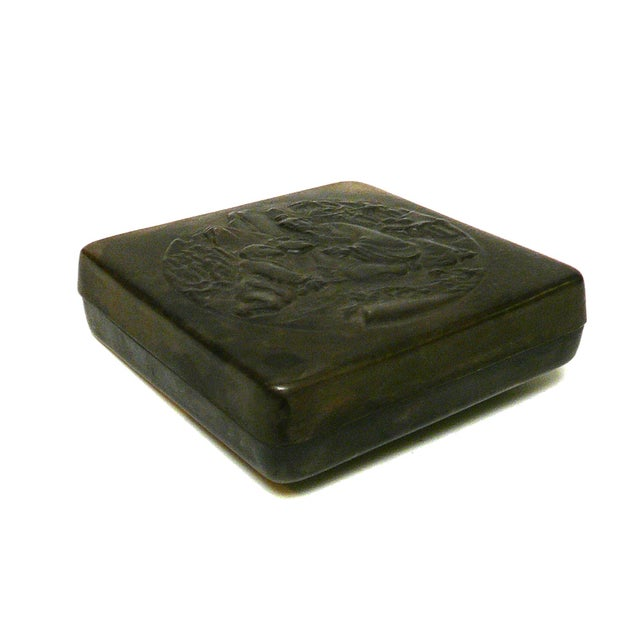 This is a handmade metal bronze color finish trinket box with oriental dimensional motif or engravement on the surface....