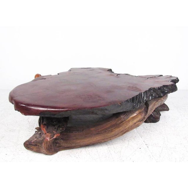 This impressive vintage coffee table features natural hardwood construction with a thick tree slab top. The amorphous live...