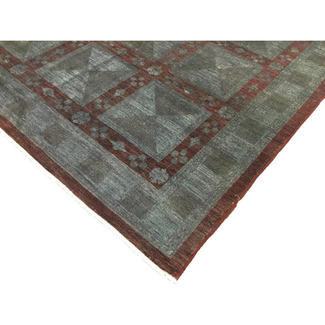 Gray with red hues and a masterful construction help make this modern hand-knotted wool rug a standout foundation for any...