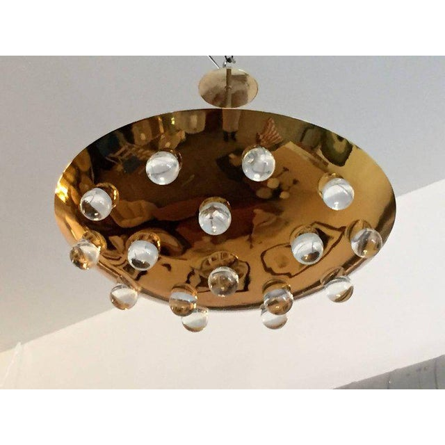 A wonderful 1960s French gold-plated brass round disc fixture with 16 solid glass orbs. Five-light sources which emit...