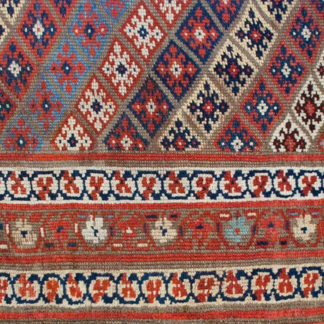 """An early 20th century Kurdish carpet with geometric floral pattern surrounded by multiple floral borders. Measures: 4'7"""" x..."""