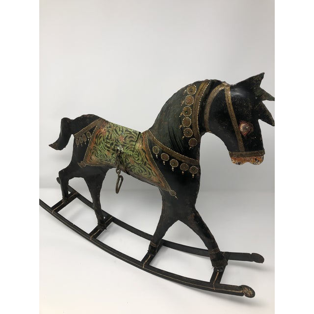 This primitive, rustic rocking horse is hand painted welded metal, is rusty and faded due to age but is a charming piece...