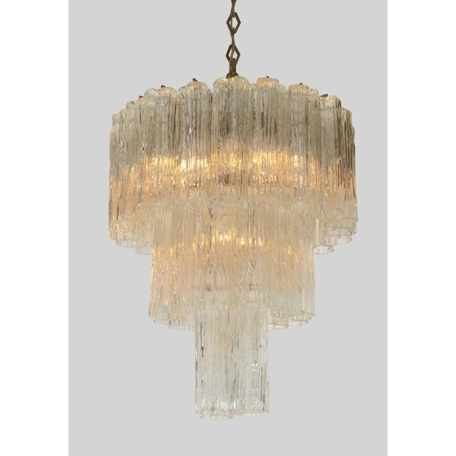A circular form chandelier comprising a metal frame containing three tiers of textured molded Tronchi glass tubes. By...