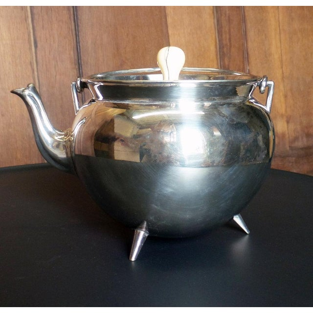 A silver plated tea-pot with cover and bone finial by of Dr. Christopher Dresser. Hallmarked.
