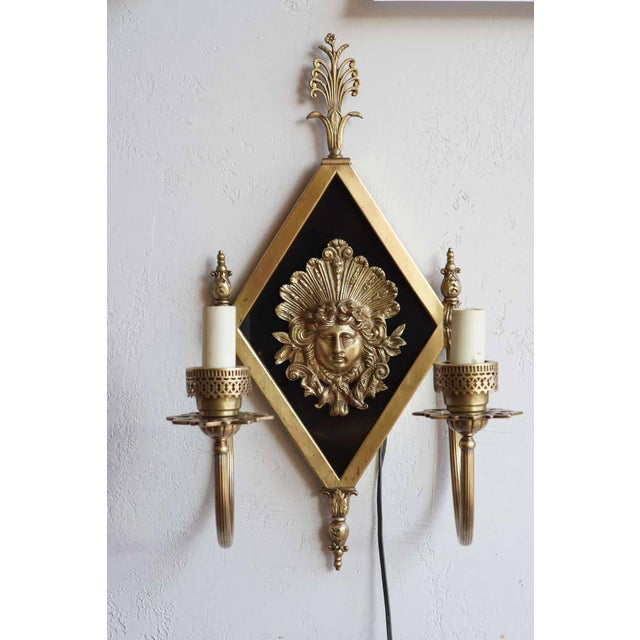 Stunning pair of early 20th century neoclassical bronze two-arm sconces showcasing a Greek goddess centerpiece. From the...
