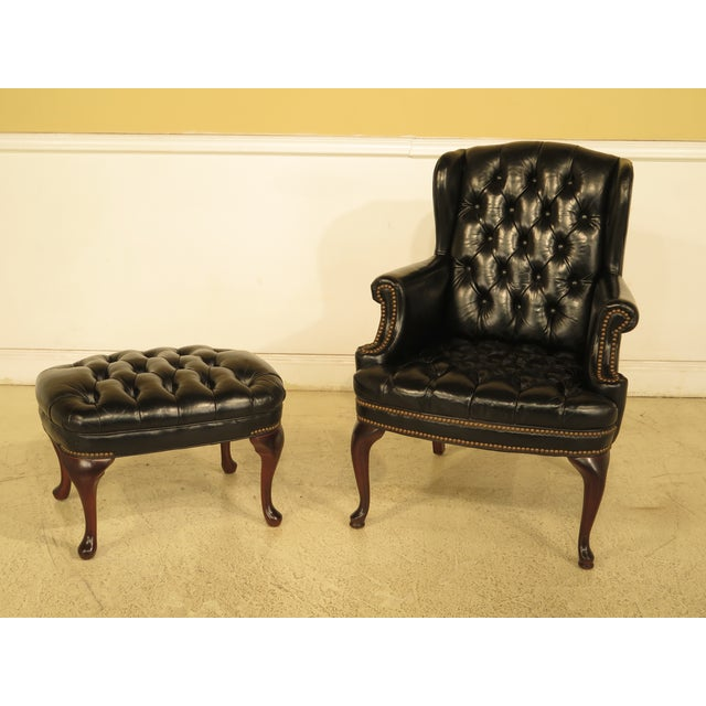 This English traditional black tufted leather wing chair and ottoman set boasts quality construction, Queen Anne legs and...