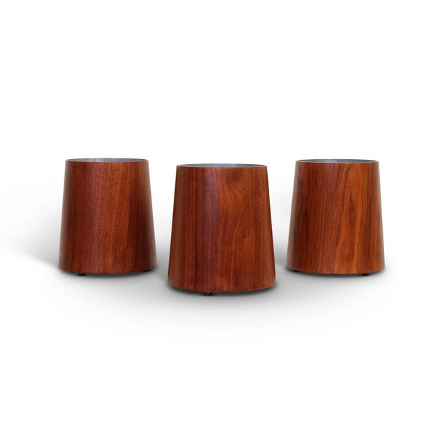 Collection of three walnut and metal wastebaskets by American designer Jens Risom. Tapering walnut exteriors with...