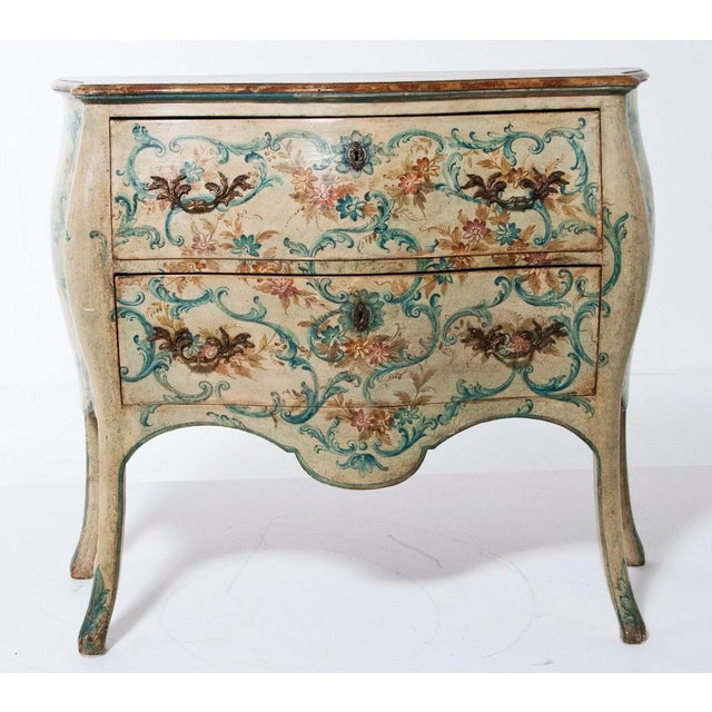A pair of mid 20th century Italian painted bombé commodes in the Louis XV style. The front and sides are painted in a...