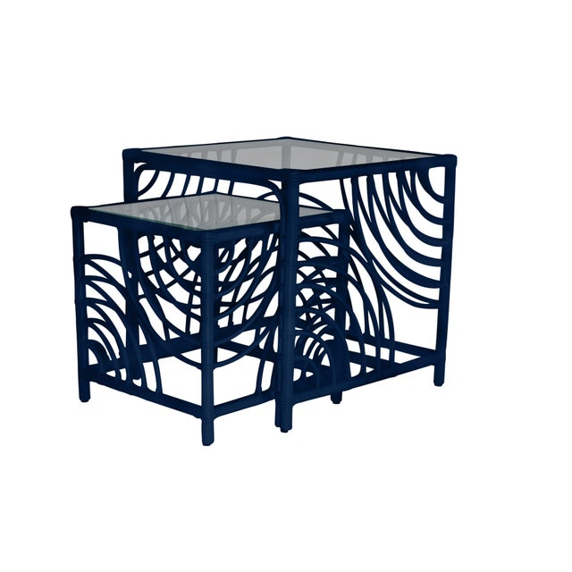 This functional and stylish two-piece nesting table features a Rattan frame with rawhide bindings and a clear, glass top....