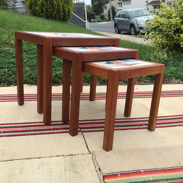 A nice set of 3 Danish teak and tile top nesting tables. Unsigned. Most likely made in Denmark. Circa 1970's. Neat hand...