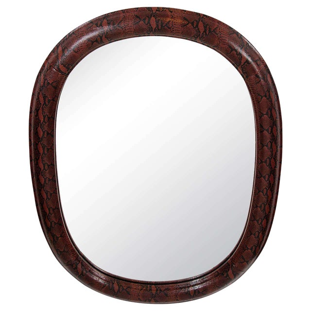 Stunning mid-century modern oval mirror with rounded frame. Wrapped in burgundy red and black embossed leather with...