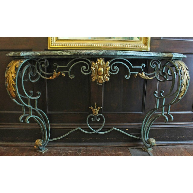 A verdigris, scrolled iron marble top console table- shaped demilune form. Gilt acanthus accents. Rococo style. Mid-20th...
