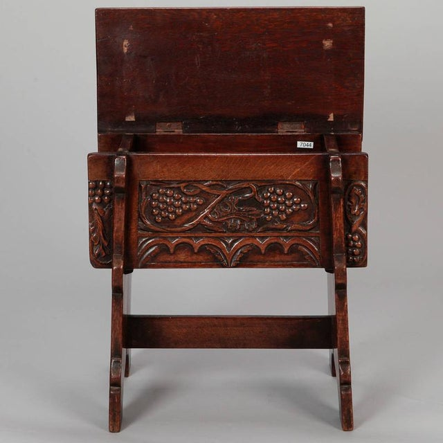 Circa 1920s French oak stool with trestle style base, hinged flip open top and carved grape details along apron. Dealer...
