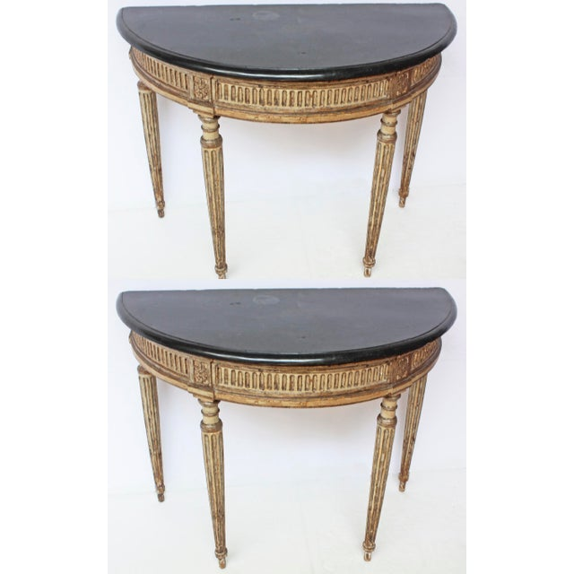 A rare pair of Italian neoclassical painted and gilded console tables in the Louis XVI style with original stone tops.