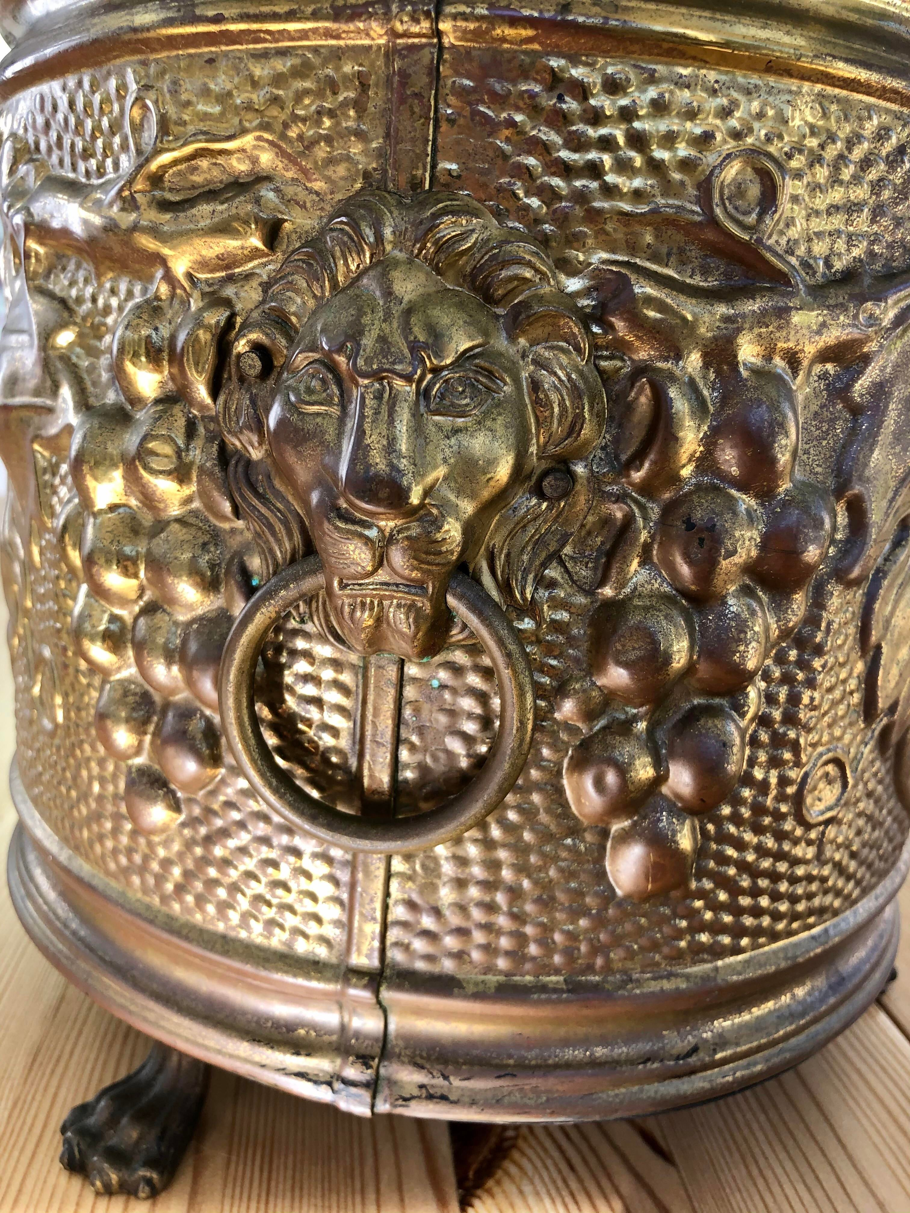 Brass footed planter with lion heads and etchings