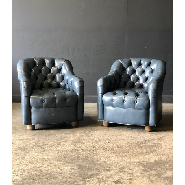 A pair of classic diamond tufted lounge chairs in sumptuous blue leather. A traditional yet luxurious addition to any room!