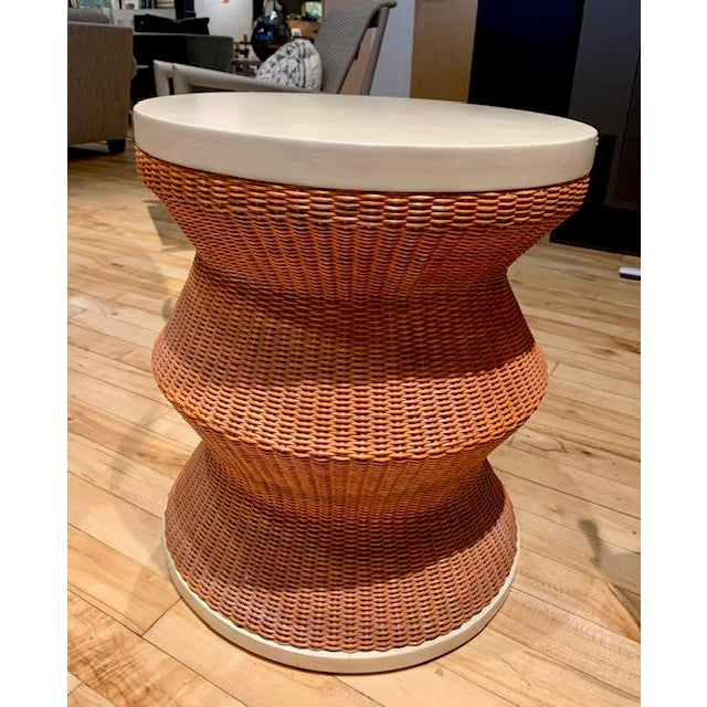 The whimsy side table has a painted wicker base and a painted resin top. The base is painted a muted orange and the top is...