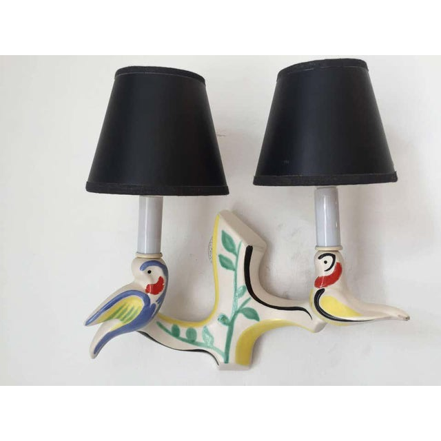 An original pair of French, 1950s handmade art pottery sconces composed of two birds holding two shades. Hand-painted and...