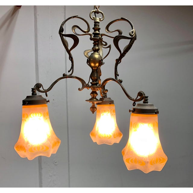 Classic Art Nouveau swoops and curls adorn this Brass Chandelier with 3 original frosted glass shades. Nice antique patina.
