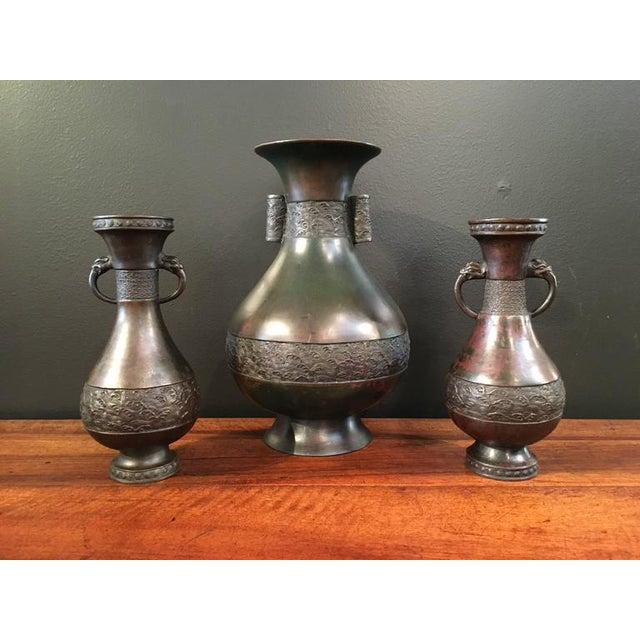 """Consisting of a large baluster vase (H: 14.25"""") with arrow handles and a near pair of smaller baluster vases with mythical..."""