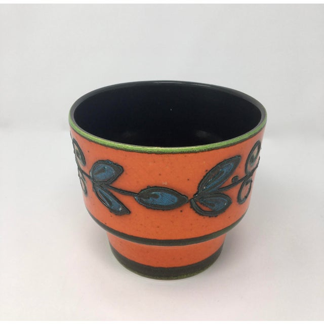 This gorgeous pot is a fine example of midcentury pottery. The exterior is glazed with a tomato red, black, chartreuse,...