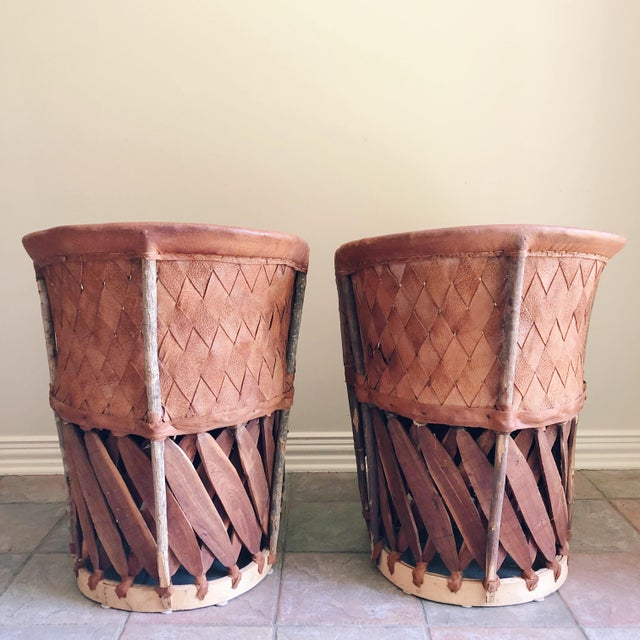 Pair of equipale chairs, with woven leather barrel backs and wood bases. Constructed with chestnut brown tanned leather,...