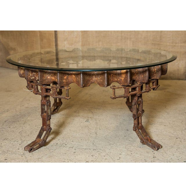 Round, vintage Industrial gear coffee table with beveled glass top. Rusted patina.