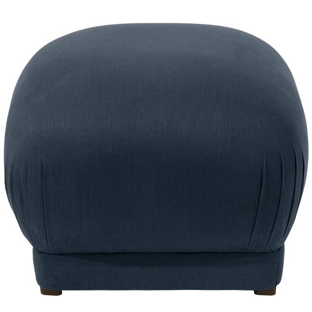 Smooth upholstery covers a sleek cushioned silhouette, accentuated at the corners with delicate handcrafted pleating. This...