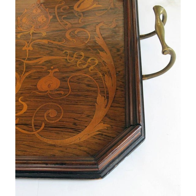 A finely inlaid French Art Nouveau rosewood rectangular tray with canted corners and brass handles; the rosewood tray...