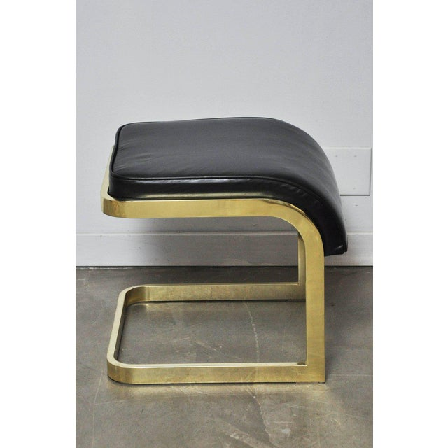 Pair of brass frame stools with new black leather cushions. Design Institute, circa 1970s.