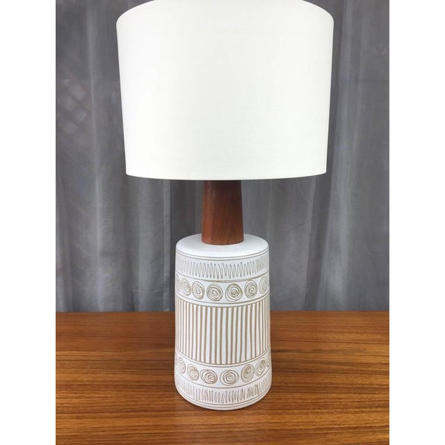 A large signed ceramic and teak table lamp by Gordon & Jane Martz for Marshall Studios. Slightly-tapered barrel base was...