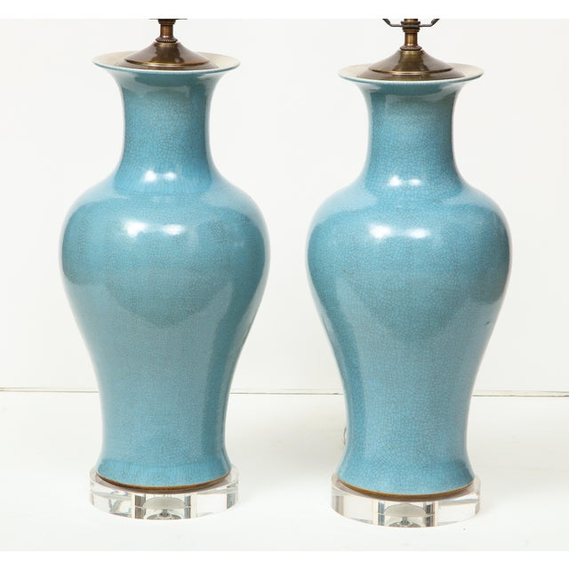 A stunning pair of Chinese ceramic lamps in a soft blue on a Lucite base. The crackle glaze on these lamps gives them such...