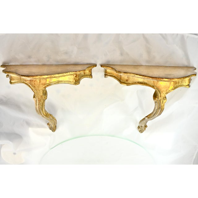 Pair of Italian Florentine hand carved gold gilt wood wall shelves. No maker's mark. Pencil dated 1975. Light wear and...