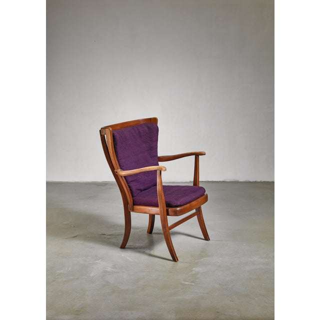 An elegant Danish wooden Mid-Century armchair with purple cushions and a wonderful warm patina in the wood. The curved...