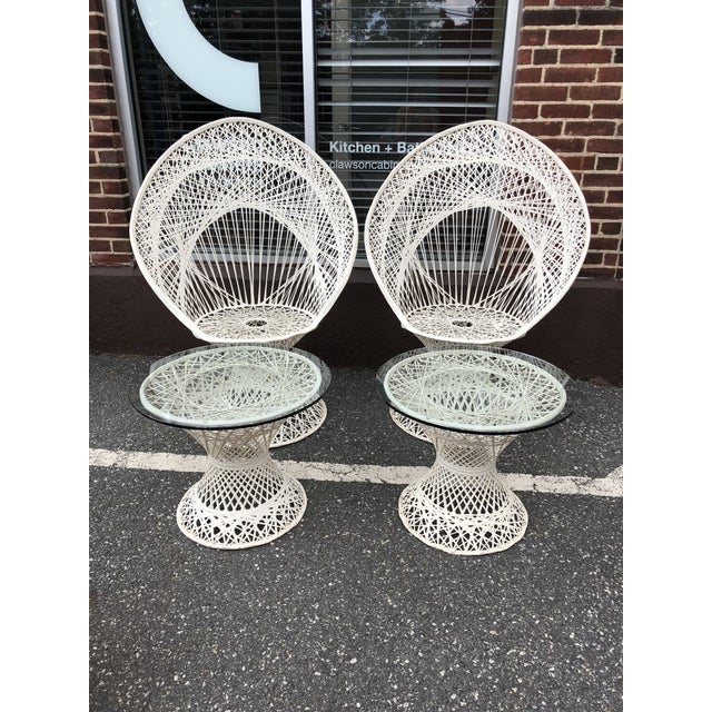 This Russell Woodard spun fiberglass furniture set includes two white peacock chairs and two matching side tables with...