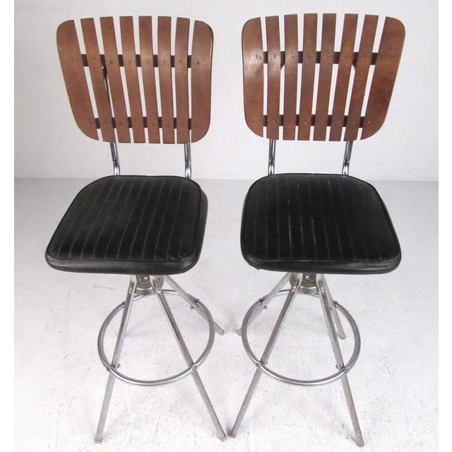 This matching pair of wood slat bar stools feature sculpted chrome bases with comfortable upholstered seats. Attractive...