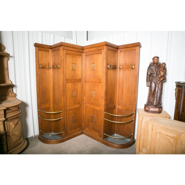 Rare and unusual French Art Deco corner coat closet from a Parisian cafe´. Triple-panel center doors with carvings open to...