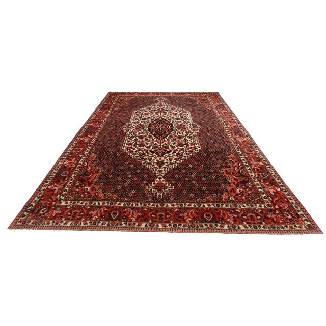Crafted of hand-knotted wool, this Persian Bakhtiari rug features a floral medallion design.