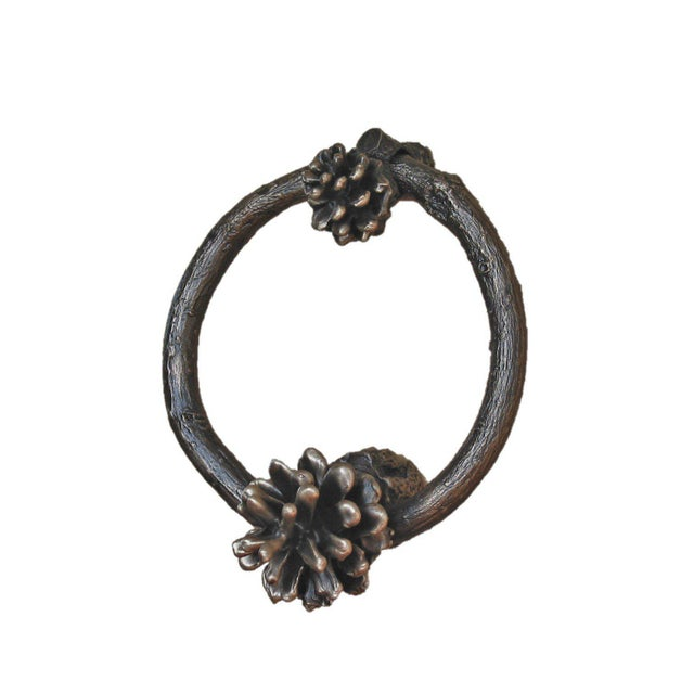 "This solid bronze, two-piece Lodgepole pine cone door knocker features a carefully crafted 3-1/2"" diameter branch ring,..."