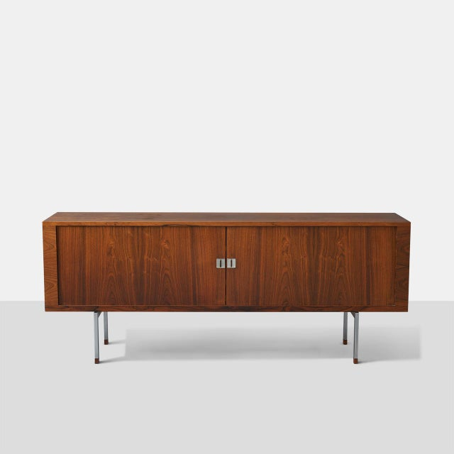 A credenza by H. J. Wegner. Features a Brazilian rosewood front with two tambour doors enclosing oak shelves and sliding...