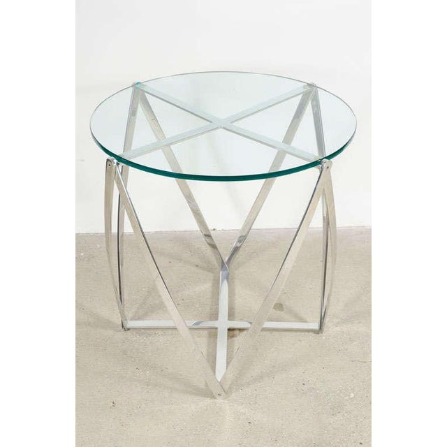 A geometric lamp table with base comprised of polished aluminum ribbons in a zig-zag formation supporting a circular glass...