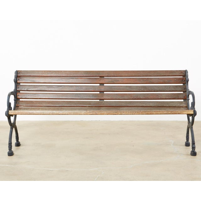 Handsome cast iron and wood slat park or garden bench made in the neoclassical taste. Features X-form Curule style legs on...