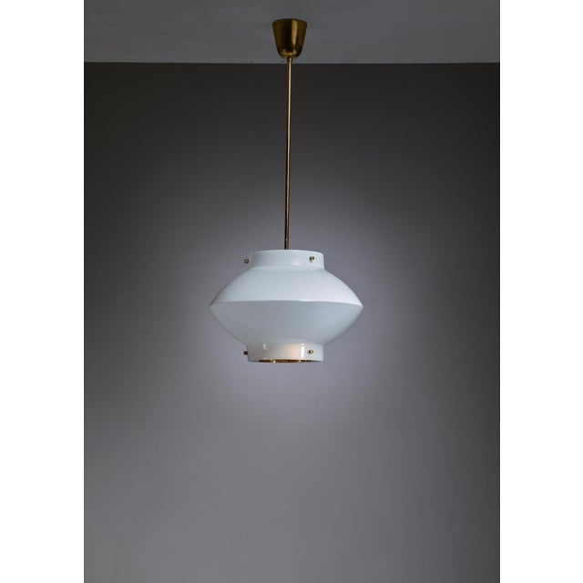 One of three white plexiglass model 61-380 pendants by Yki Nummi for Orno, Finland. The lamp has a brass ceiling mount and...