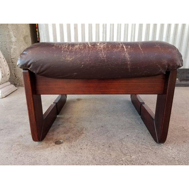A leather and rosewood footstool / ottoman by Percival Lafer, circa. 1970s. Original leather seat with wear and patina, no...