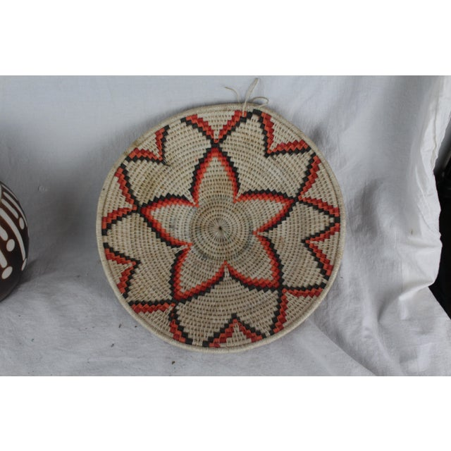 Handwoven grass African tribal basket with floral pattern in hues of brown, tan, and orange. Made in the mid 20th century.