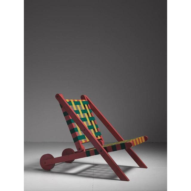 A folding lounge chair, made of a red painted pine frame with a backrest and seating made of green and yellow parachute...