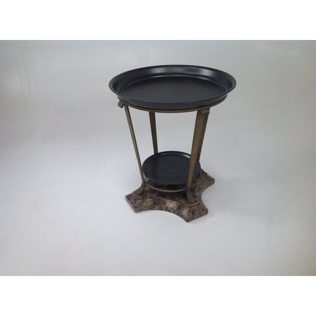 Unique claw foot side table with iron top and stand. The bottom is travertine and the top is a round tray. The table is in...